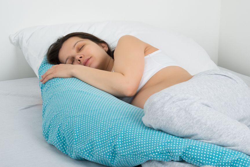 Schwangere Frau schläft in Seitenlage mit Stillkissen