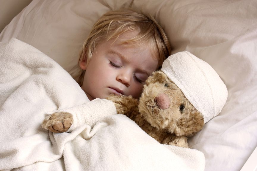 Kind schläft mit Teddy im Arm