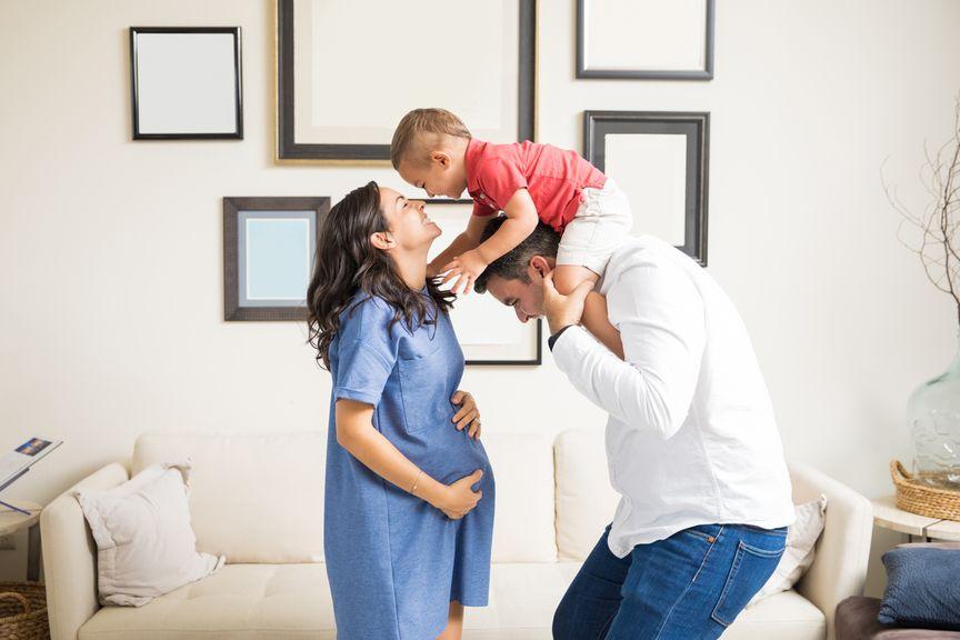 Schwangere Frau küsst Kind auf Papas Schultern