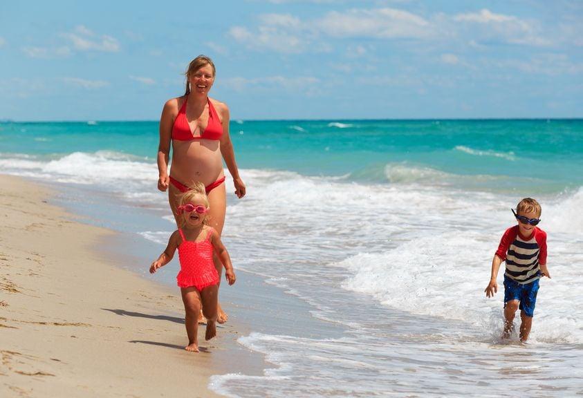Mutter und Kinder spazieren am Strand im Wasser