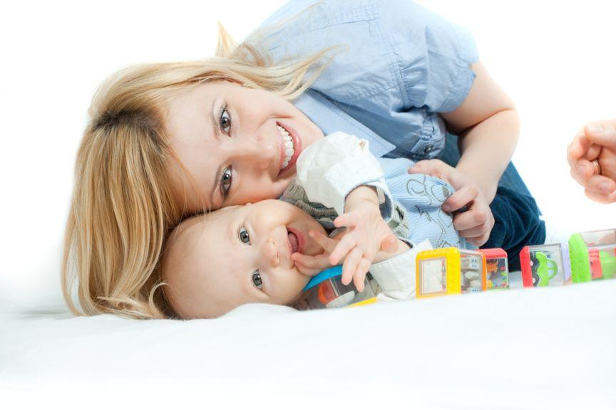 Mutter mit Baby schmusen am Boden