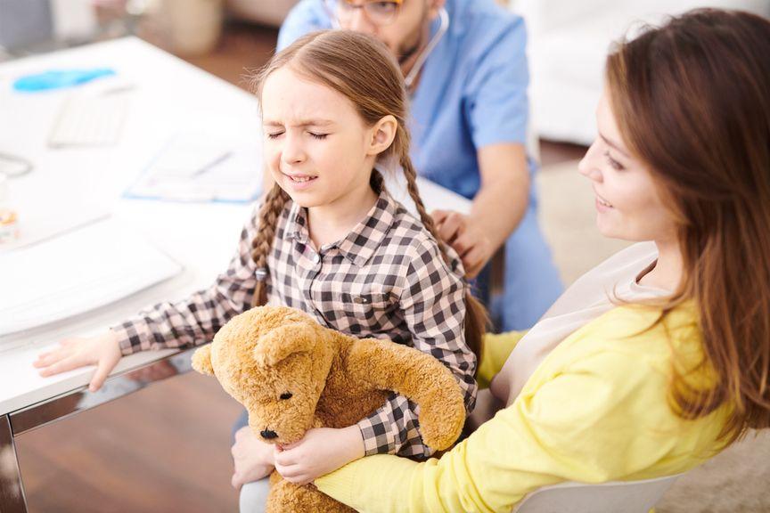 Kind mit Schmerzen wird in einer Arztpraxis untersucht