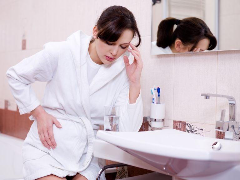 Schwangere sitzt auf der Badewanne und hält sich Bauch und Stirn
