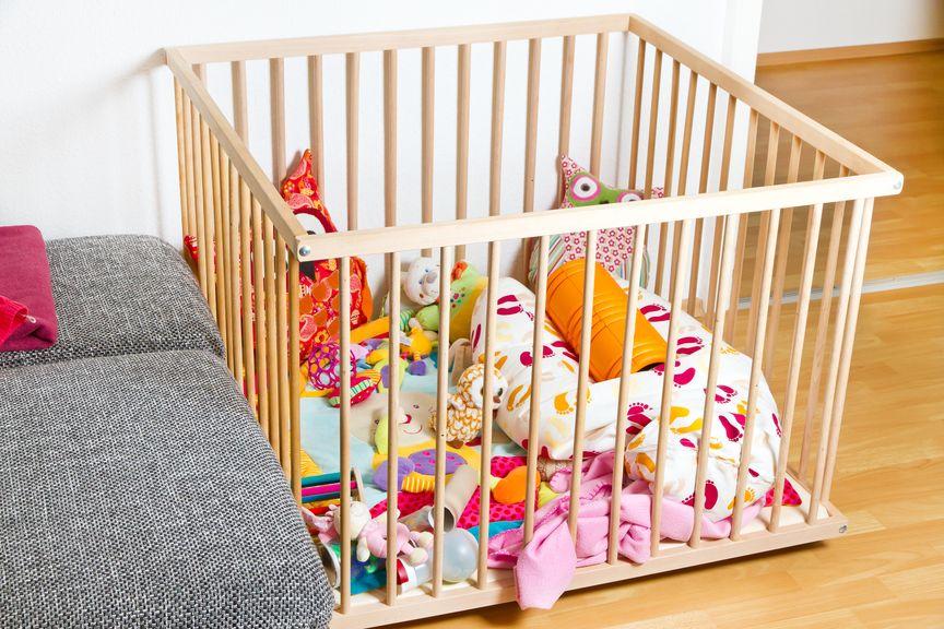 Laufgitter im Wohnzimmer mit Kissen und Spielzeug