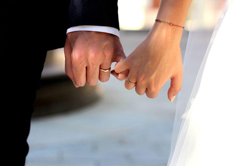 Hände mit Eheringen eines Hochzeitspaares