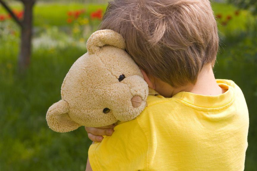 Kind mit Kuscheltier an der Schulter