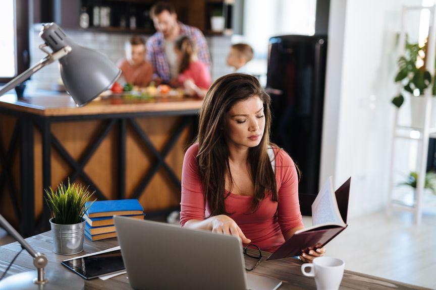 Mutter ist am Laptop, Vater ist mit den Kindern in der Küche,[Translate to FR:] IStock 1157909291