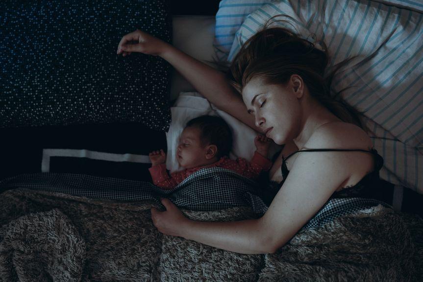 Mutter und Säugling schlafen im Elternbett