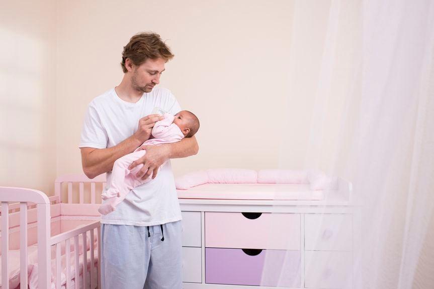 Vater gibt Baby im Kinderzimmer stehend den Schoppen