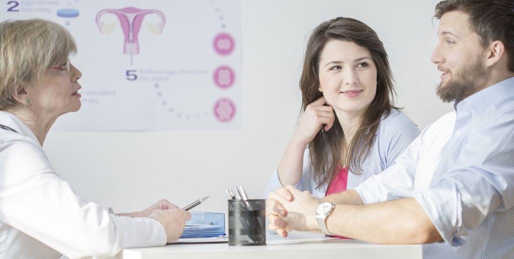 Paar in der gynäkologischen Praxis zusammen mit der Ärztin am Besprechen