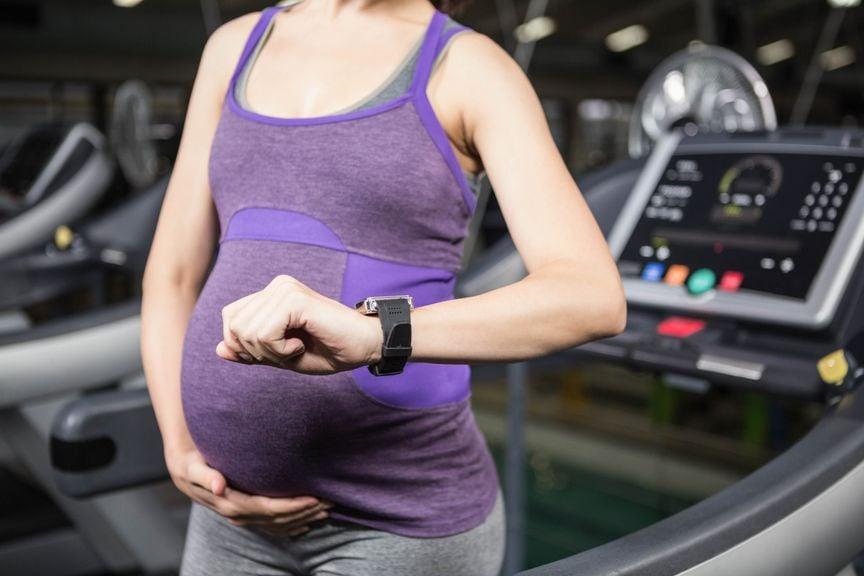 Schwangere schaut im Fitnessstudio auf ihre Armbanduhr