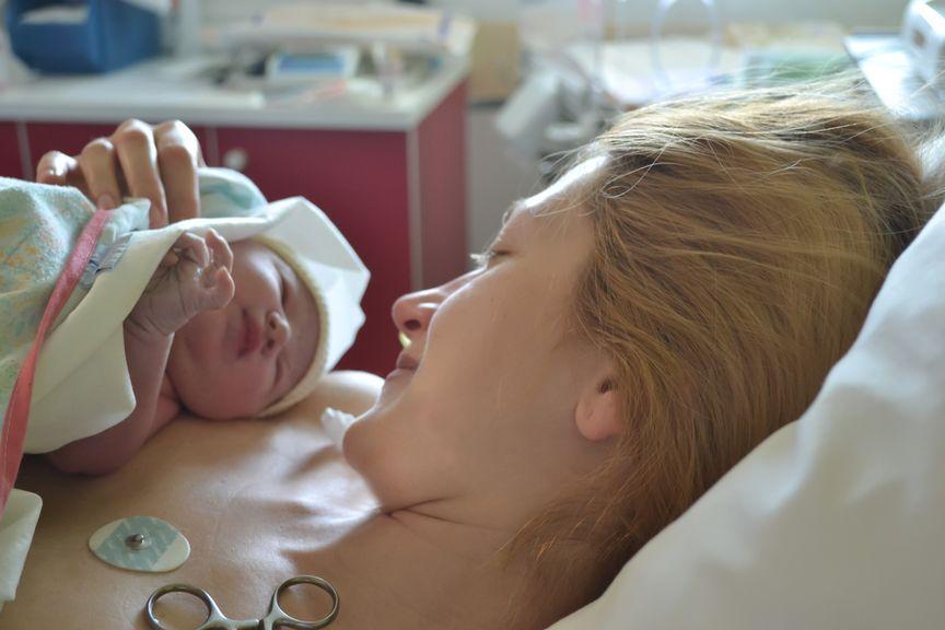 Neugeborenes in den Armen der Mutter Minuten nach der Geburt