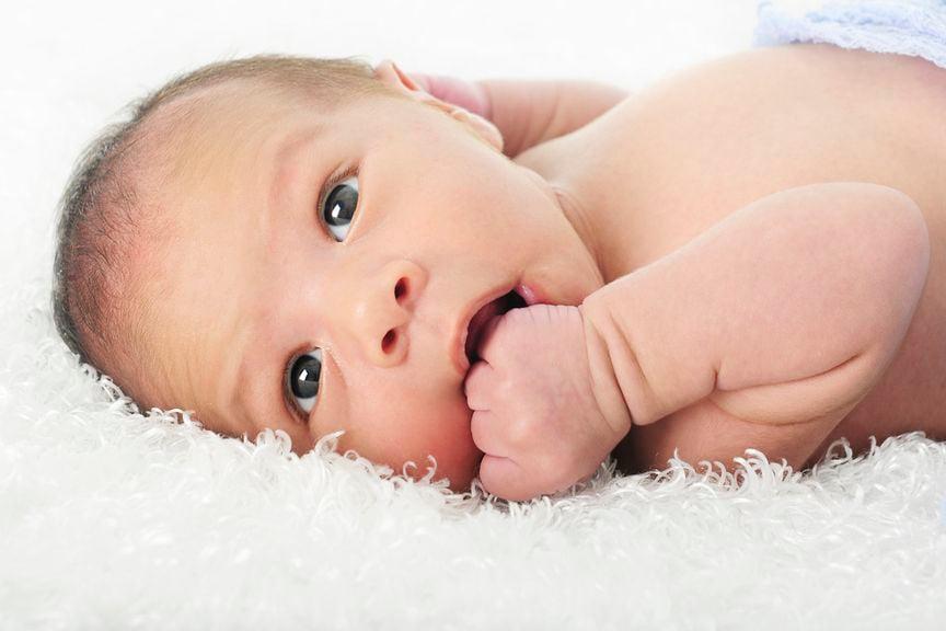 Wacher Säugling mit den Fingern am Mund