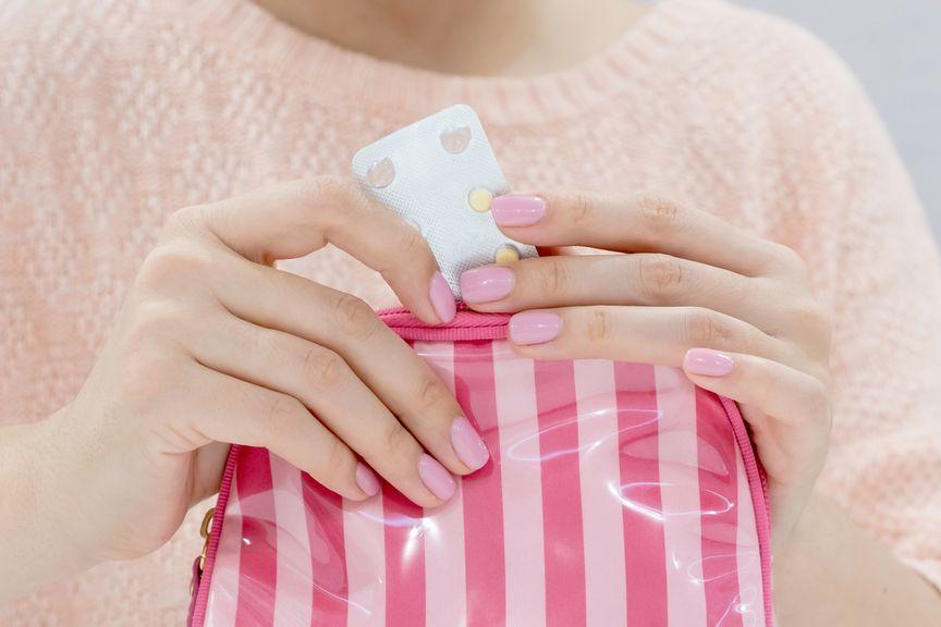 Frau nimmt Tablette aus dem Necessaire