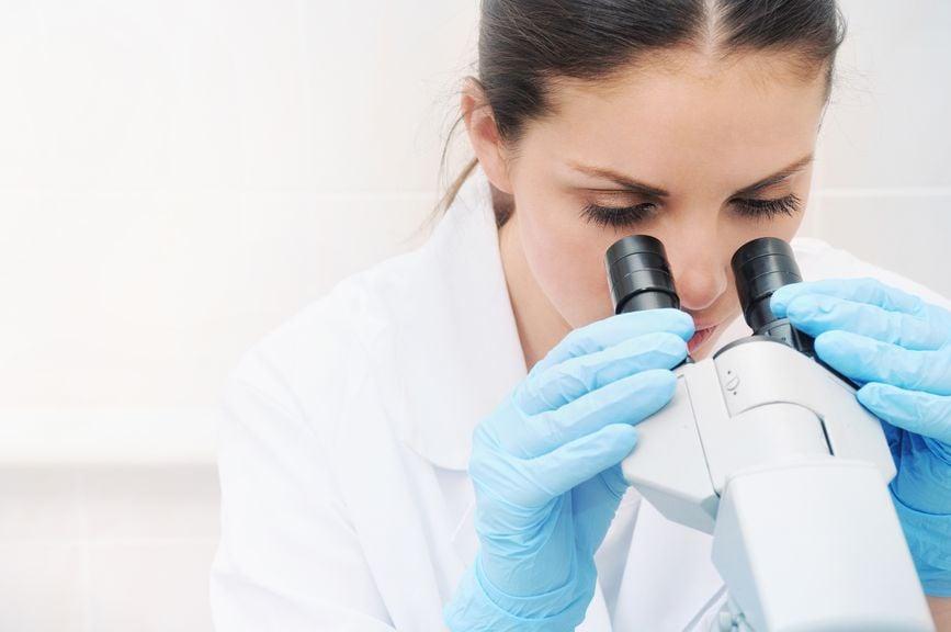 Frau schaut in das Mikroskop
