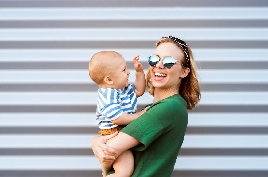 Frau mit Sonnenbrille und Baby auf dem Arm