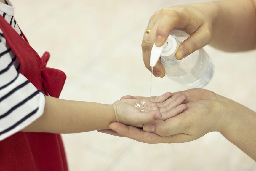 Frau gibt Desinfektionsmittel in eine Kinderhand