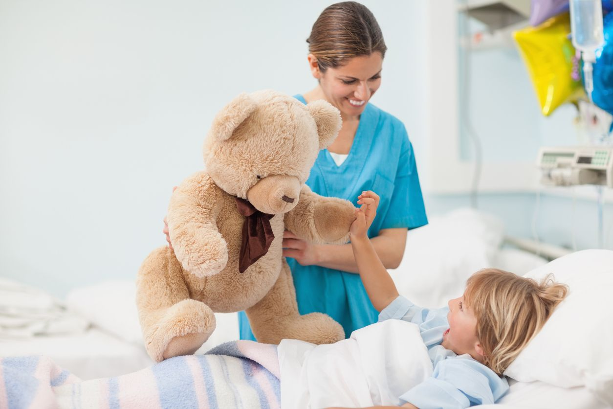 Pflegefachfrau mit Teddy am Spitalbett