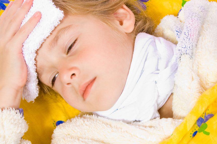 Kind mit Waschlappen auf der Stirne und Halstuch im Bett