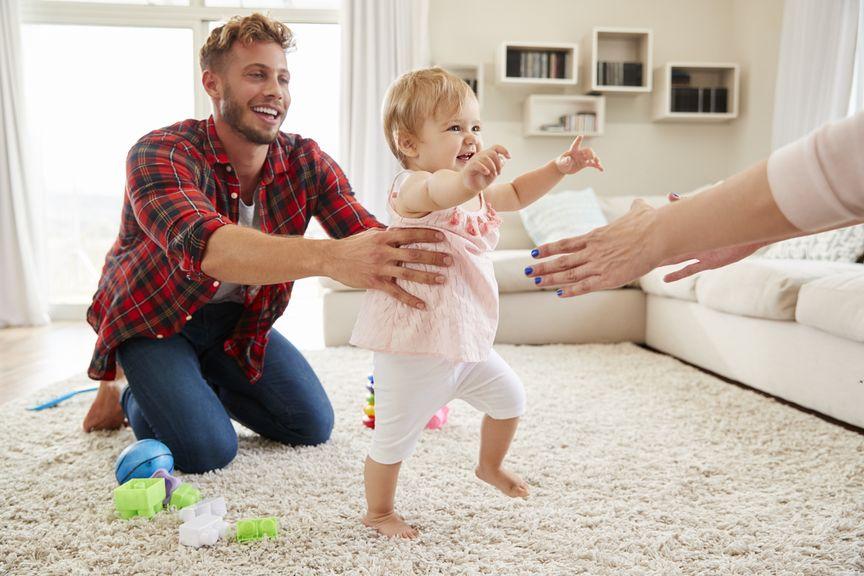 Baby macht erste Schritte zwischen den Eltern