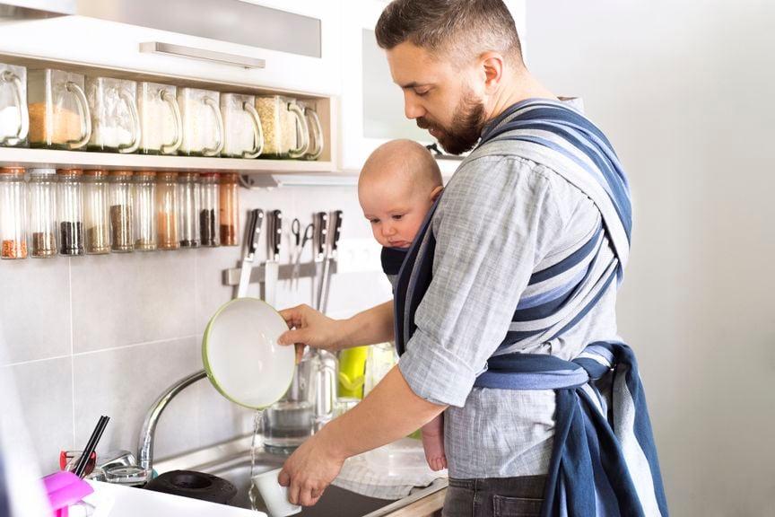Vater mit Baby im Tragetuch spült Geschirr
