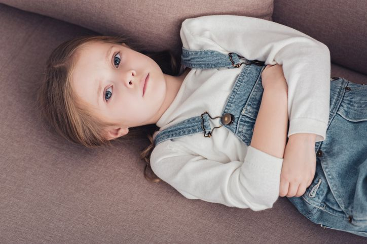 Kind liegt auf dem Sofa