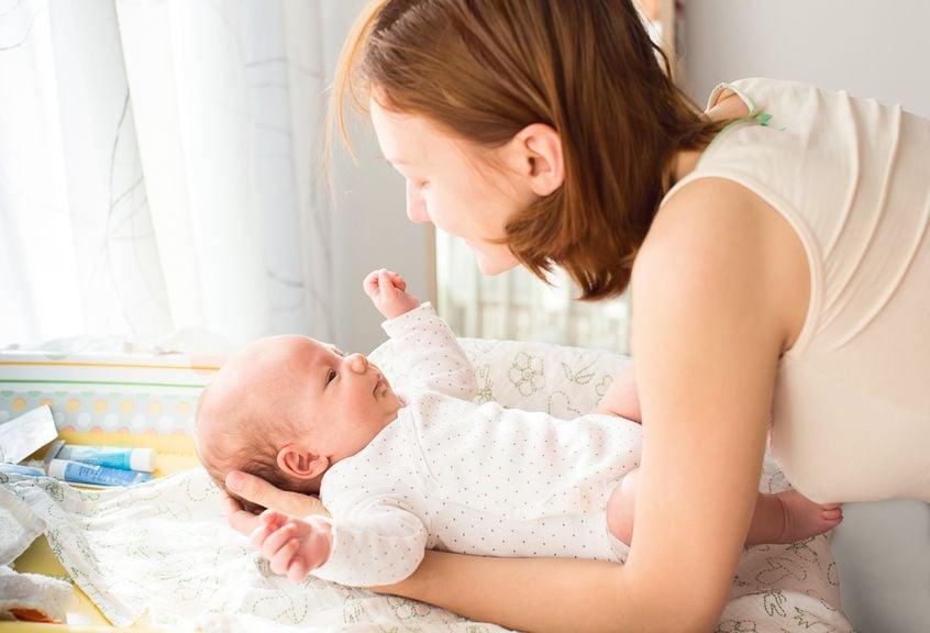 Mutter legt ihren Säugling behutsam auf den Wickeltisch