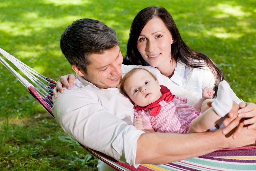 Paar mit Baby in der Hängematte im Garten