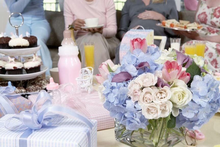 für Babyshower gedeckter Tisch, im Hintergrund die Schwangere