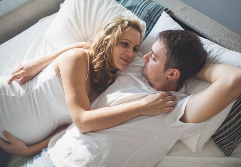 Schwangere und Mann im Bett