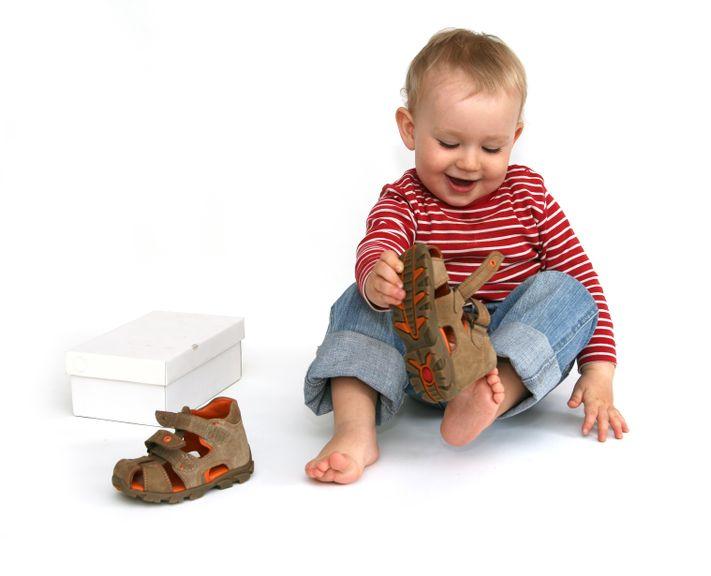 Kind probiert selber die Schuhe
