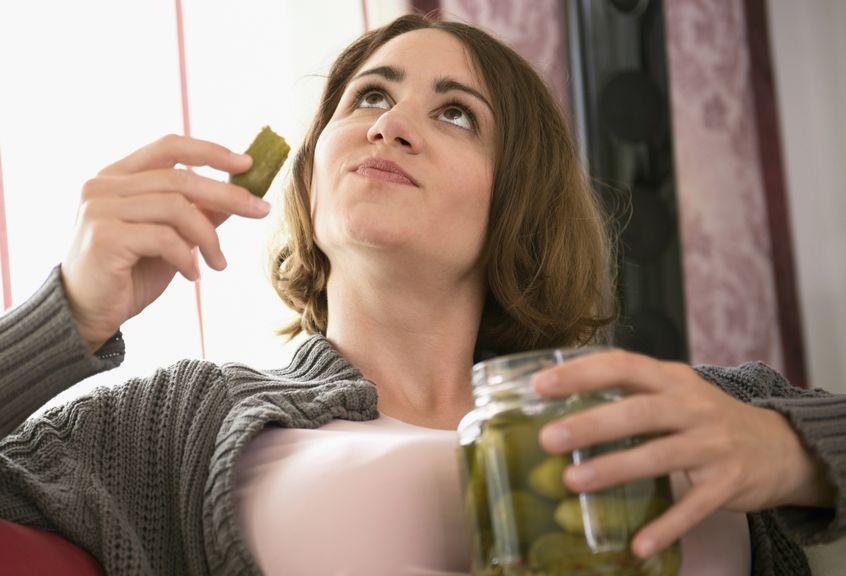 Frau isst eine Essiggurke