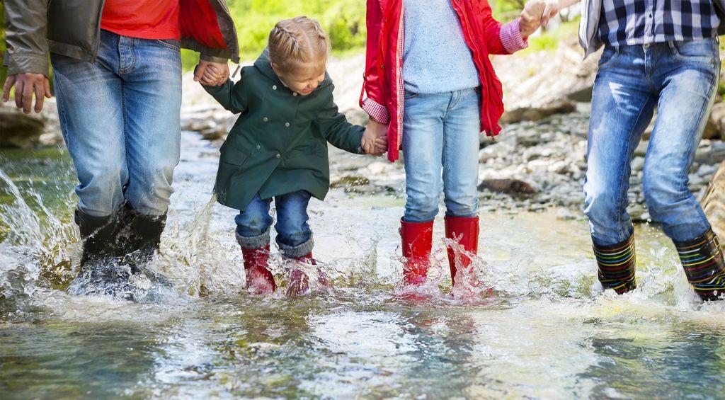 Familie mit Gummistiefeln im Wasser