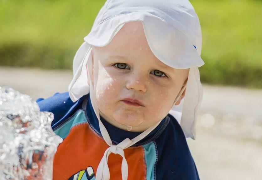 Kind mit Sonnenhut und UV-Badeanzug