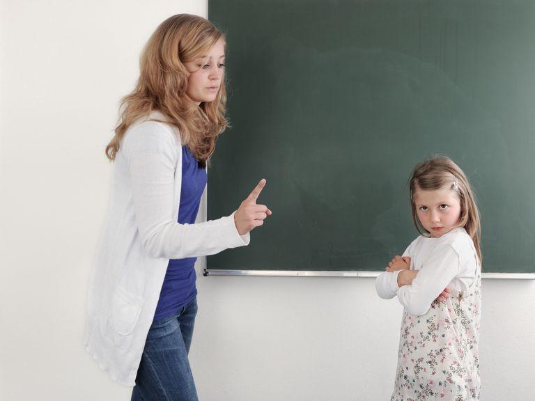 Lehrerin erhebt mahnend den Zeigefinger gegenüber einer Schülerin