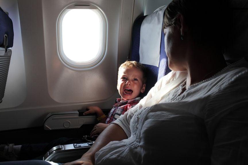 Kind sitzt neben der Mutter im Flugzeug und weint