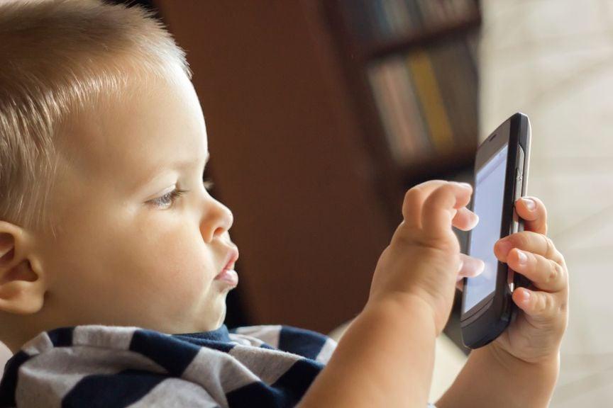 Kind tippt mit dem Finger auf dem Handy