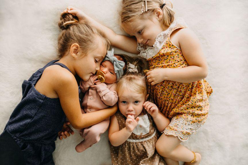 Drei kleine Mädchen mit dem vierten Geschwisterkind
