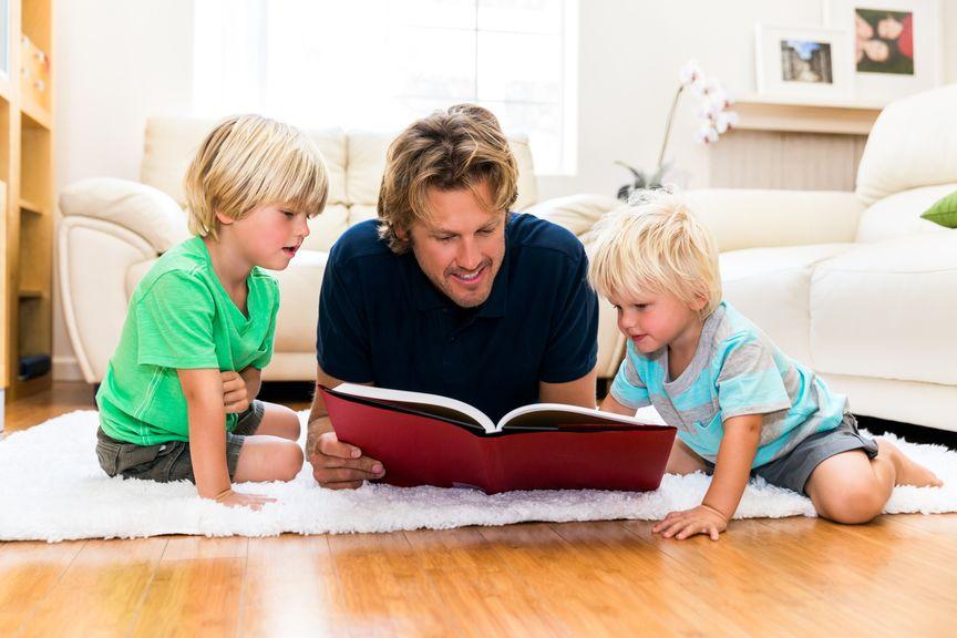 Vater liest seinen beiden Kindern auf dem Boden vor