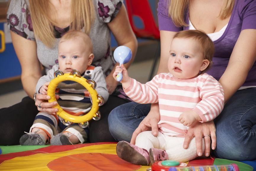 Baby mit Musikinstrumenten am Boden sitzend