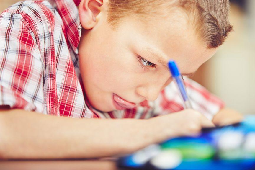 Schulkind strengt sich an beim Schreiben