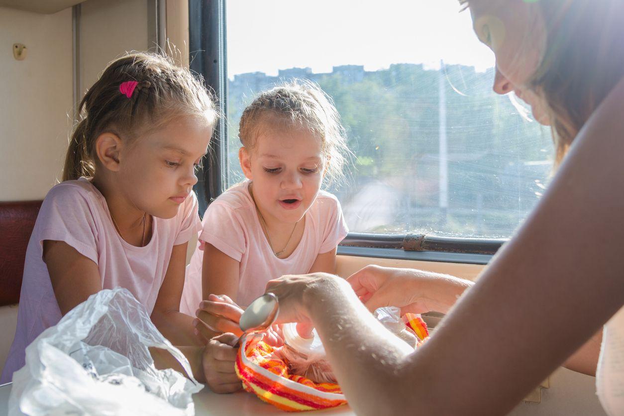 Mutter und Kinder essen im Zug