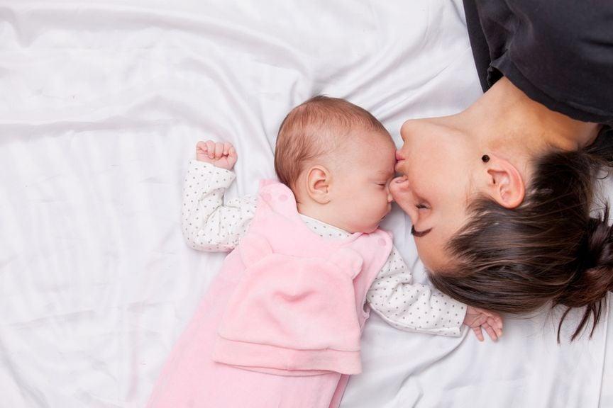 Mutter und Baby im Elternbett, Mutter küsst Baby auf die Stirn