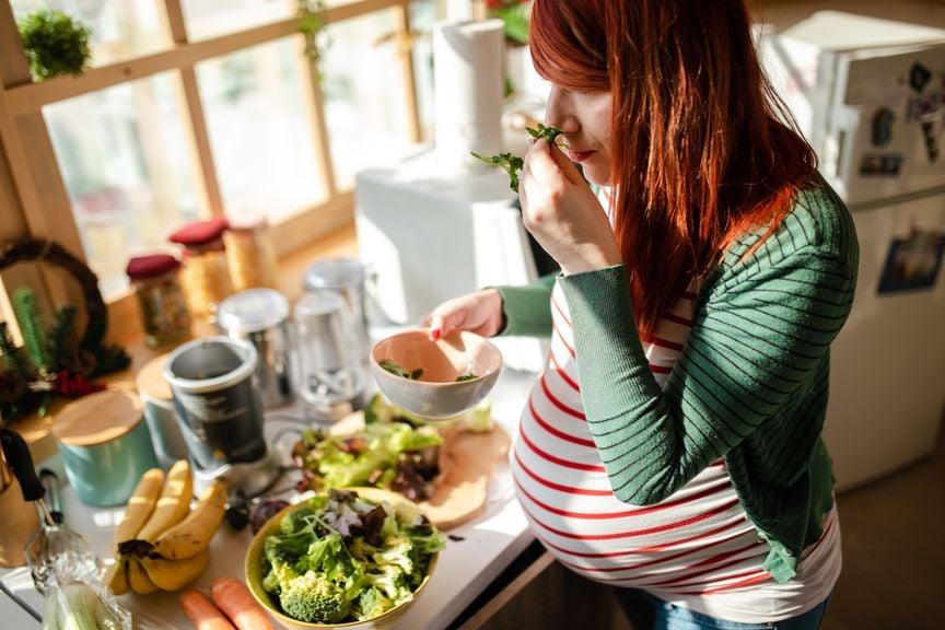 Schwangere riecht am Essen