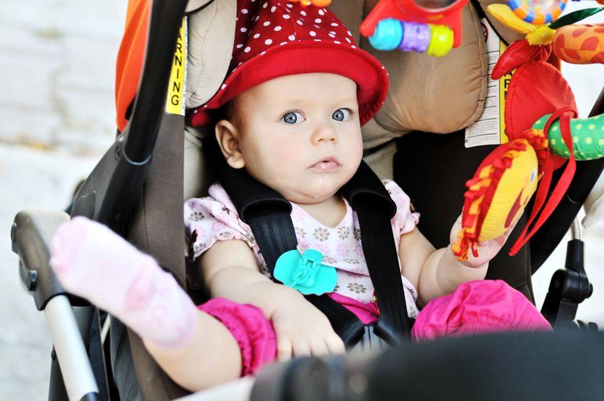 Baby mit Hut sitzt im Buggy