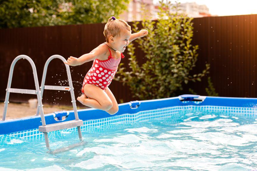 Kind springt in den Gartenpool