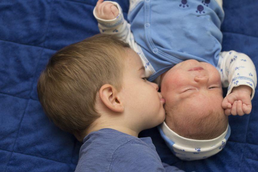 Geschwister küsst Neugeborenes