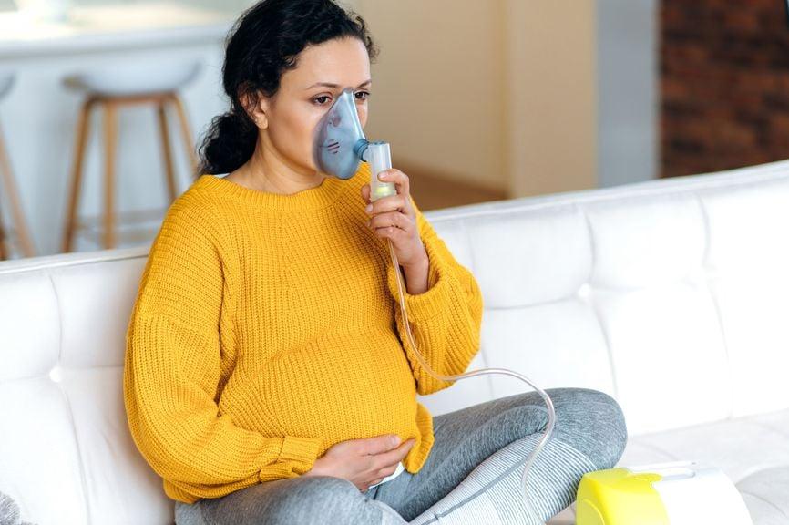Schwangere inhaliert mit Dampfinhalator
