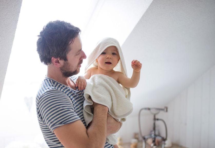 Vater trocknet nach dem Baden das Baby ab
