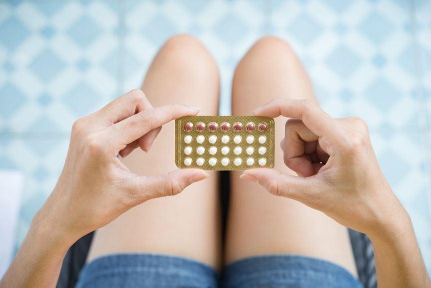 Frau hält Pillenblister mit beiden Händen